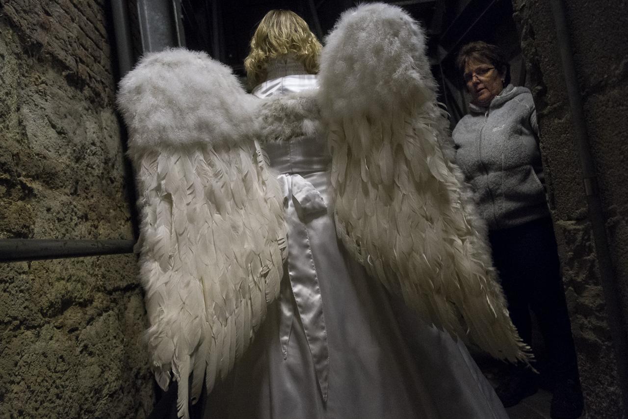 Die Engeldarstellerin der lebendigen Krippe in Zons hat Schwierigkeiten die Treppen hinter der Bühne hochzusteigen.